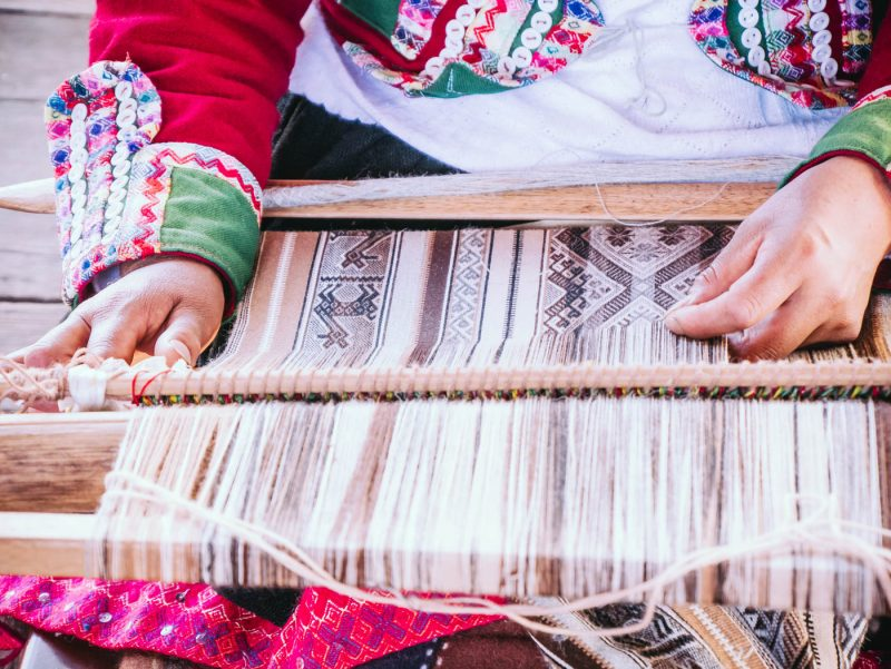 Artisan woman weaving fabric at Mundo Alpaca